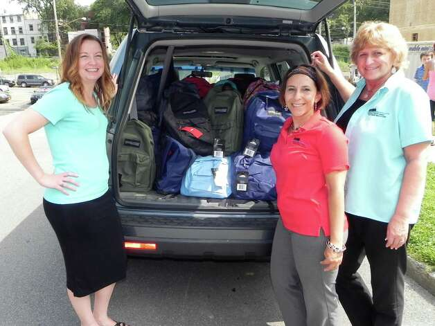 Community Resource Federal Credit Union's employees unload 100 backpacks for the students in the Sheridan Hollow neighborhood of Albany. From left are Heather Parent, Deana Harrington and Sue Munks (Wendy Meola)