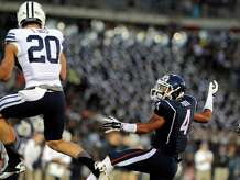 Connecticut wide receiver Deshon Foxx (4) watches as a pass intended for him is intercepted by BYU defensive back Craig Bills (20) during the first half of an NCAA college football game in East Hartford, Conn., Friday, Aug. 29, 2014.