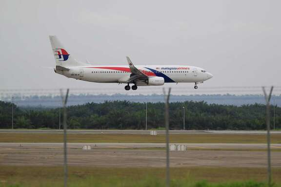 A Malaysia Airlines plane approaches Kuala Lumpur International Airport in Sepang, Malaysia, on Friday. Malaysia Airlines will cut 6,000 workers as part of an overhaul to revive its damaged brand.