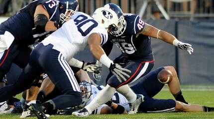 Connecticut tight end Sean McQuillan (49) and BYU tight end Matt Sumsion (80) fight for a loose ball after a Connecticut fumble during the first half of an NCAA college football game in East Hartford, Conn., Friday, Aug. 29, 2014.