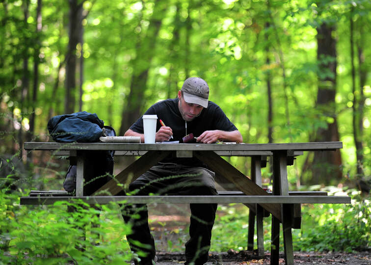 Derek Renninger, of Bethel, spends some time studying the Bible at one of the picnic benches at Over