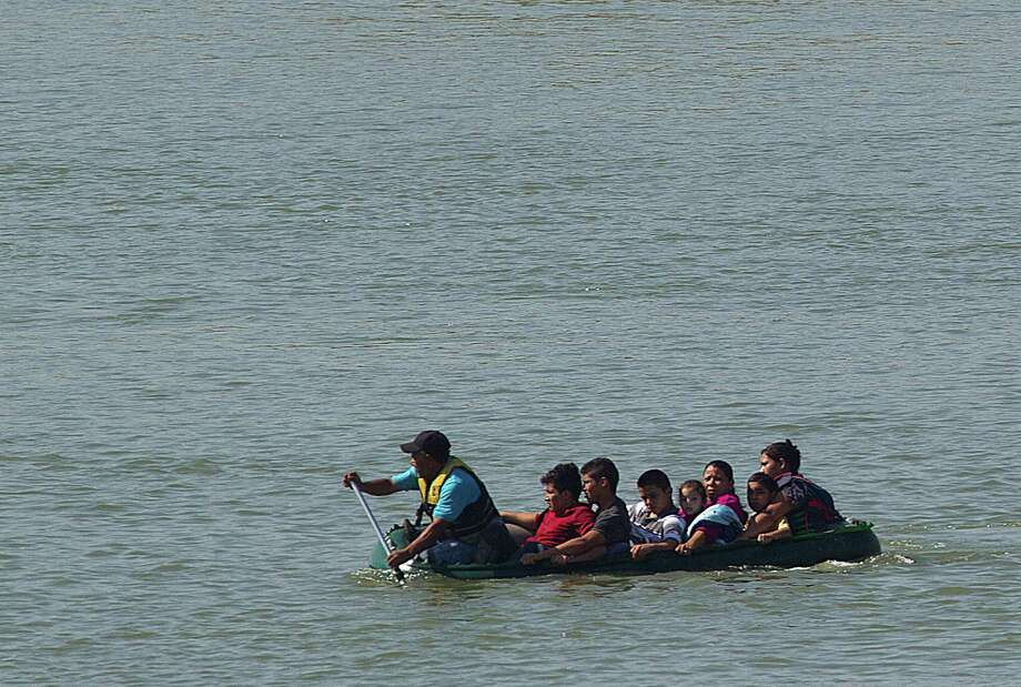 A group of seven people are smuggled from Mexico across the Rio Grande River near Mission in May. The group from El Salvador and Honduras included two mothers each with a child, and an 11-year-old boy and two 17-year-olds who said they were heading to Houston and Maryland. Photo: Johnny Hanson / © 2014  Houston Chronicle