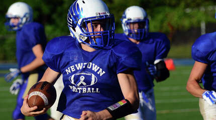 Newtown's Troy Frangione carries the ball to the endzone for a touchdown, during football scrimage action against Westhill in Newtown, Conn. Friday, Aug. 29, 2014.