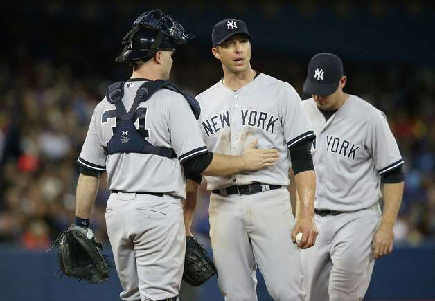 TORONTO, CANADA - AUGUST 29: Chris Capuano #26 of the New York Yankees gets a pat from Brian McCann #34 moments before being relieved in the seventh inning during MLB game action against the Toronto Blue Jays on August 29, 2014 at Rogers Centre in Toronto, Ontario, Canada. (Photo by Tom Szczerbowski/Getty Images) ORG XMIT: 477588937 Photo: Tom Szczerbowski / 2014 Getty Images