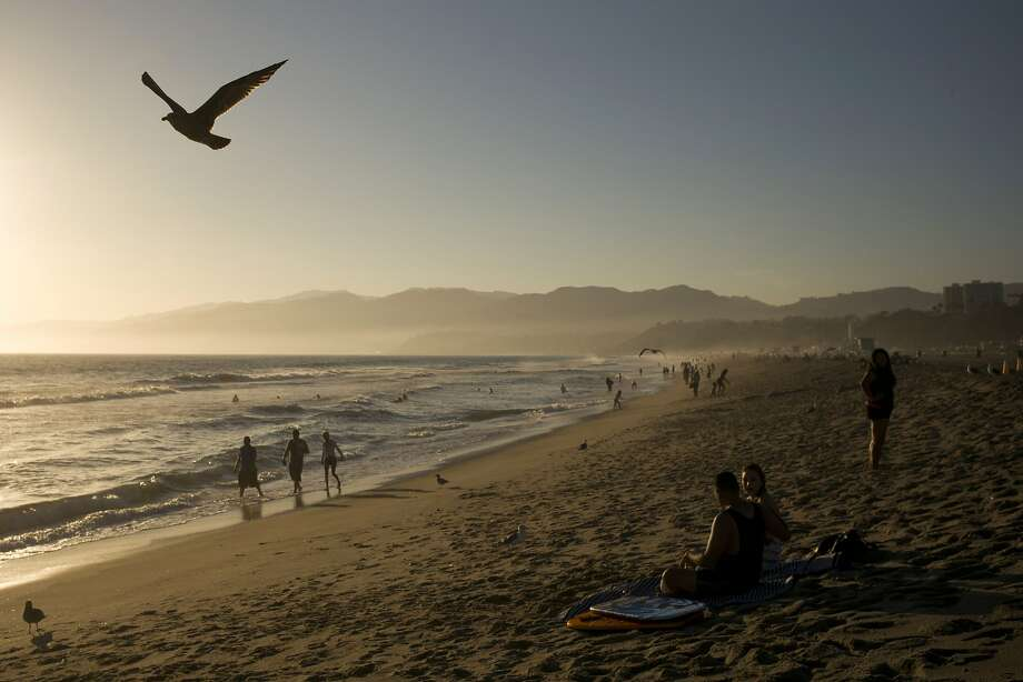 People walk along the beach Friday, Aug. 29, 2014, in Santa Monica, Calif. The highest number of Californians since the recession is expected to travel over the Labor Day holiday weekend. (AP Photo/Jae C. Hong) Photo: Jae C. Hong, Associated Press