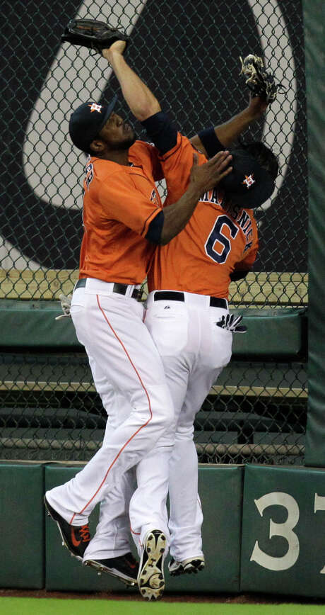 Astros center fielder Dexter Flower, left, tangles with right fielder Jake Marisnick as Marisnick makes a catch on a fly ball hit by the Rangers' Adrian Beltre during the first inning of Friday night's game. Photo: Melissa Phillip, Staff / © 2014  Houston Chronicle