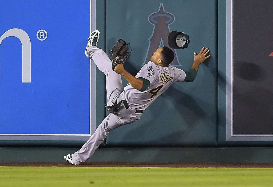 Coco Crisp failed to hold the ball when he crashed into the wall. It fell over for Chris Iannetta's fifth-inning homer. Photo: Mark J. Terrill, Associated Press