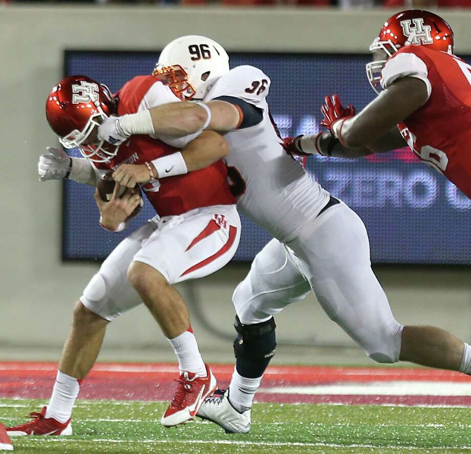 UTSA defensive tackle Jason Neill (center) sacks Houston quarterback John O'Korn in Houston's TDECU Stadium. O'Korn threw four picks, and the Cougars had six turnovers. Photo: Brett Coomer, Houston Chronicle / © 2014  Houston Chronicle