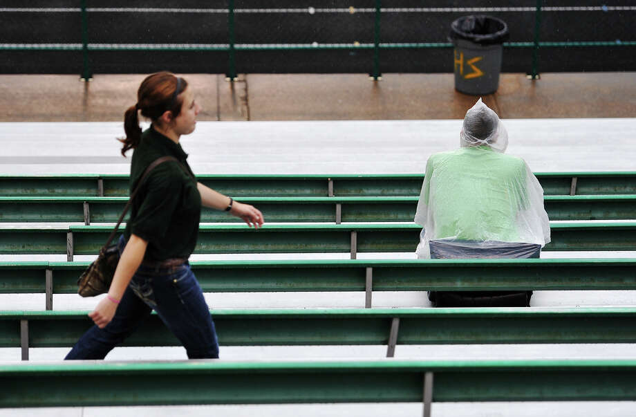 Fans move to their seats during Friday's pre-game drizzle at Little Cypress-Mauriceville. West Orange-Stark played their opening game of the 2014 season against Little Cypress-Mauriceville at LC-M on Friday night. Photo taken Friday 8/29/14 Jake Daniels/@JakeD_in_SETX Photo: Jake Daniels / ©2014 The Beaumont Enterprise/Jake Daniels
