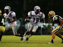 West Orange-Stark's Will Johnson looks for a hole in the line of scrimmage during Friday's game against Little Cypress-Mauriceville. West Orange-Stark played their opening game of the 2014 season against Little Cypress-Mauriceville at LC-M on Friday night. Photo taken Friday 8/29/14 Jake Daniels/@JakeD_in_SETX