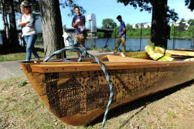 A paper boat, formed from an REI canoe, features the drawings of local artist Patrick Porter on Saturday, Aug. 30, 2014, at the Troy Town Dock and Marina in Troy, N.Y. The boat is in the SeaChange 2014 flotilla to raise awareness about climate change. (Cindy Schultz / Times Union) Photo: Cindy Schultz / 00028395A