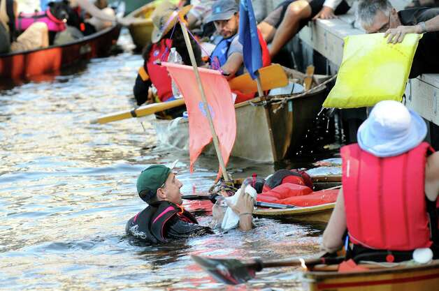 Shawn Forno of Brooklyn, center, lands in the drink when his paper canoe tips as SeaChange 2014 prepares to launch a paper boat flotilla on Saturday, Aug. 30, 2014, at the Troy Town Dock and Marina in Troy, N.Y. The flotilla will go down the Hudson River from Troy to New York City. (Cindy Schultz / Times Union) Photo: Cindy Schultz / 00028395A