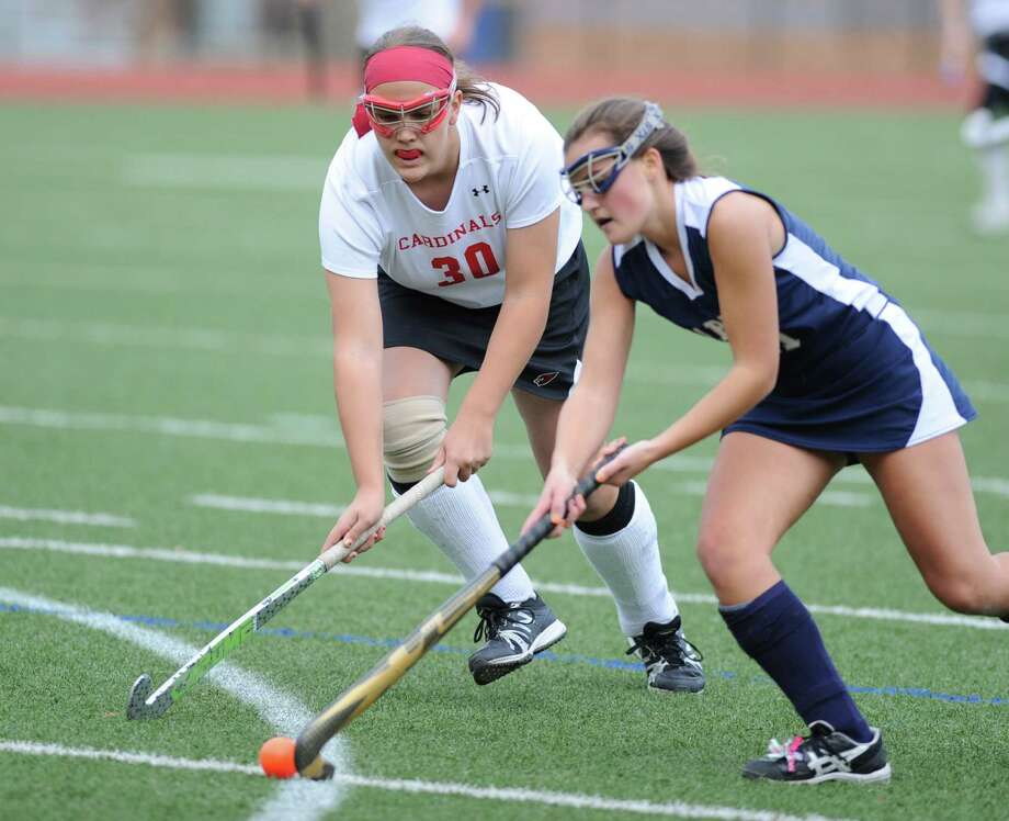 At left, Sarah Cicchetti (# 30) of Greenwich goes for the ball against Meg Fay (# 11) of Staples during the Class L field hockey playoff between Greenwich High School and Staples High School at Greenwich, Wednesday, Nov. 6, 2013. Greenwich won the match over Staples, 3-1. Photo: Bob Luckey / Greenwich Time