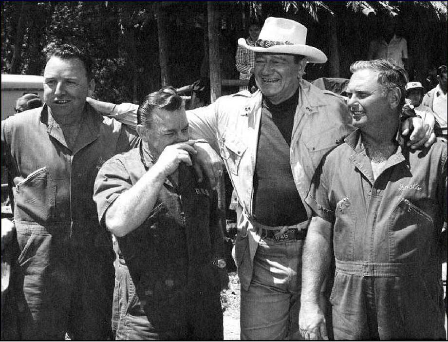 "Oil well firefighters E.O. ""Coots"" Matthews, left, Paul ""Red"" Adair and Asger ""Boots"" Hansen, right, join a white-hatted John Wayne on the set of the  1968 movie ""Hellfighters,"" in which Wayne portrayed Adair. Adair, Matthews and Hansen served as technical advisers on the film, which got the Hollywood treatment of the life of the legendary Adair. / handout"