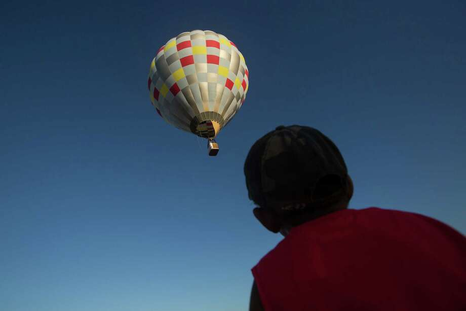 A young boy watches as a hot air balloon rises during the annual Big Bend Balloon Bash in Alpine, Texas on Saturday, Aug. 30, 2014. Photo: Courtney Sacco, Associated Press / Odessa American