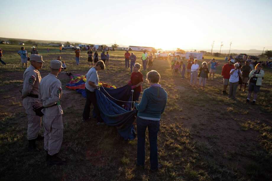 The Confetti hot air balloon team from Austin, Texas,  unwraps their balloon as they prepare to launch during the annual Big Bend Balloon Bash in Alpine, Texas on Saturday, Aug. 30, 2014. Photo: Courtney Sacco, Associated Press / Odessa American