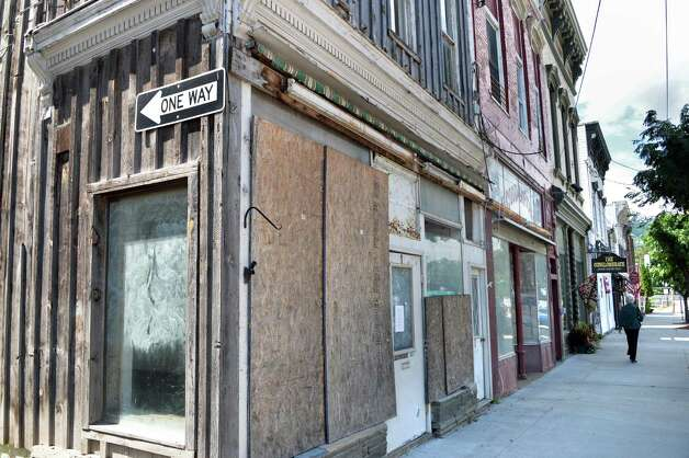 The boarded up facade of the former Good Earth Store next to Hubie's Restaurant on Main St. Thursday, Aug. 28, 2014, in Middleburgh, N.Y.  (John Carl D'Annibale / Times Union) Photo: John Carl D'Annibale / 00028363A