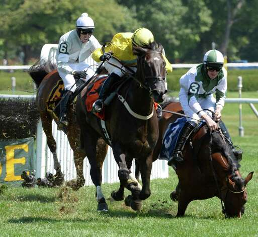 #7 Demonstrative with jockey Robert Walsh runs on after the final fence with the ill-fated #3 Makari falling with jockey Jack Doyle in the 73rd running of the New York Turf Writers Cup Aug, 25, 2014, at Saratoga Race Course in Saratoga Springs, N.Y.  Makari lost his footing on the other side of the fence and unseated the rider as he went to the ground. He did not get up.  (Skip Dickstein/Times Union) Photo: SKIP DICKSTEIN