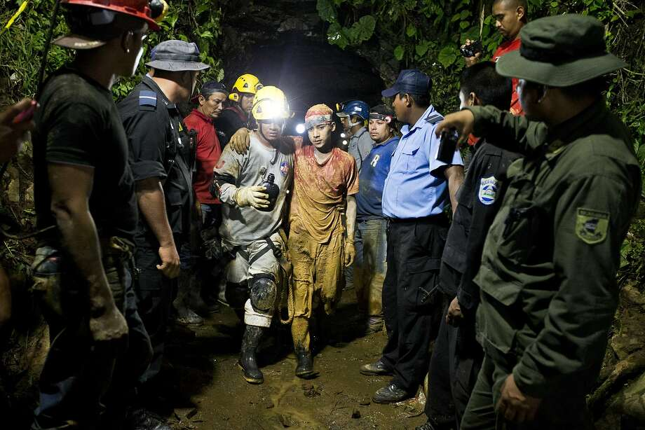 Leber Vivas Gonzales (center right), 16, exits a mine in Bonanza, Nicaragua, with the help of a rescuer. Photo: Esteban Felix, Associated Press