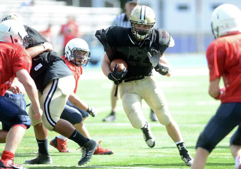 Trumbull's Adam Angelucci carries the ball Saturday, Aug. 30, 2014, during a football scrimmage with