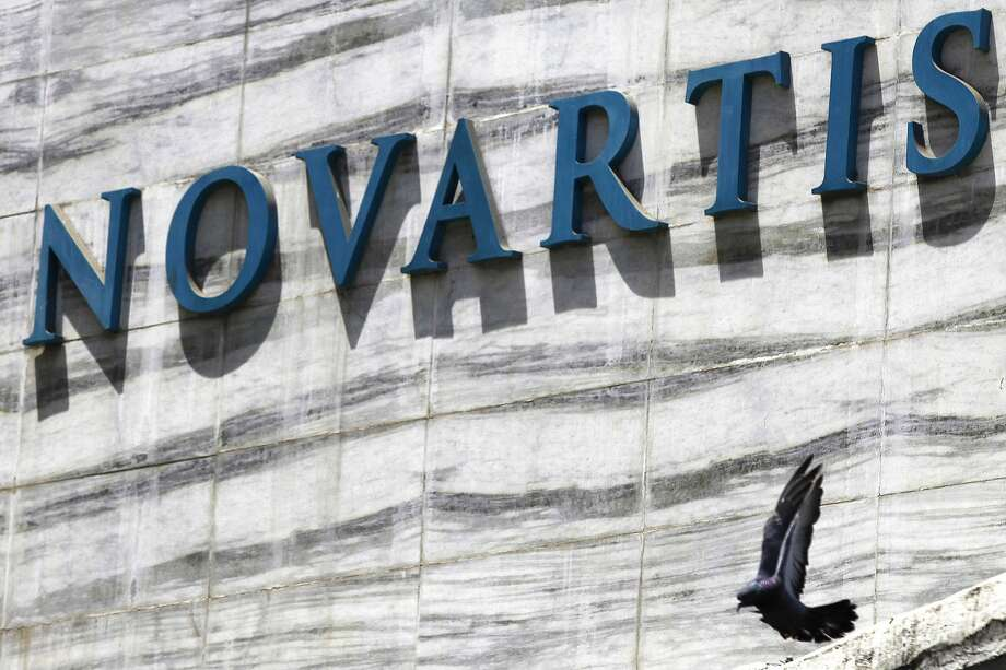 FILE - In this April 1, 2013 file photo, a dove flies near the logo of Novartis India Limited at their head office in Mumbai, India. A new study released Saturday, Aug. 30, 2014, shows an experimental Novartis drug, which does not have a name, lowered the chances of death or hospitalization by about 20 percent. (AP Photo/Rafiq Maqbool, File) Photo: Rafiq Maqbool, Associated Press