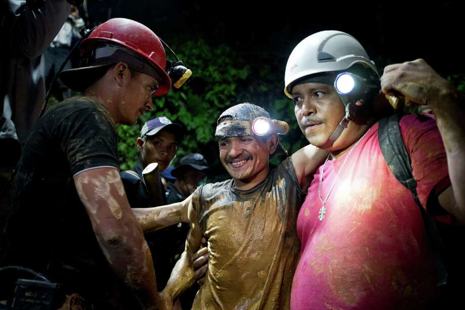 A rescued miner, center, is greeted by another miner while being helped by a rescue worker as he leaves the El Comal gold and silver mine in Bonanza, Nicaragua, Friday, Aug. 29, 2014.  The first 11 of 24 freelance gold miners trapped by a collapse in a mine have been rescued and crews were working early Saturday to free more, officials said. (AP Photo/Esteban Felix) Photo: Esteban Felix, STF / AP