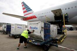 American Airlines is carrying more cargo on its new planes. Cargo is loaded onto DFW-Shanghai 777-300ER for its flight earlier this summer. American and US Airways completed a merger nine months ago.