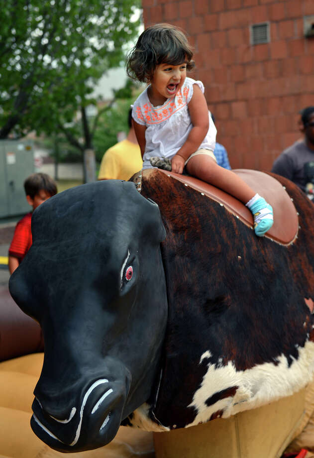 Maya Douglass, 2, of Weston, tries to hang on while riding the kids mechanical bull, during the 7th Annual Blues Views and BBQ Festival at the Levitt Pavillion in Westport, Conn. on Saturday, Aug. 30, 2014. Maya wasn't in any danger though, because the operator turned the speed down. Photo: Christian Abraham / Connecticut Post