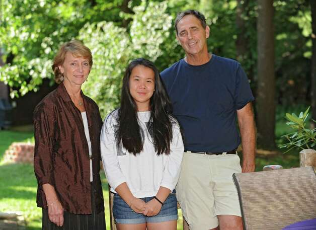 Loretta and Kenneth Ebert stand with their daughter Kaili, 13, who was adopted from China Wednesday, Aug. 6, 2014 in Ballston Lake, N.Y. The couple enrolled Kaili in Chinese language classes. (Lori Van Buren / Times Union) Photo: Lori Van Buren / 00028057A