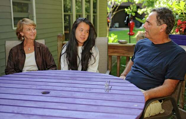 Loretta and Kenneth Ebert chat with their daughter Kaili, 13, who was adopted from China while sitting in their back yard Wednesday, Aug. 6, 2014 in Ballston Lake, N.Y. The couple enrolled Kaili in Chinese language classes. (Lori Van Buren / Times Union) Photo: Lori Van Buren / 00028057A