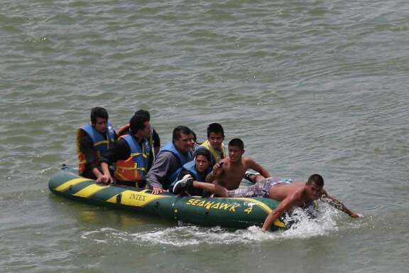 Using an inflatable raft, coyotes, or smugglers, carry immigrants across the river by the international bridge on the Rio Grande in Roma.