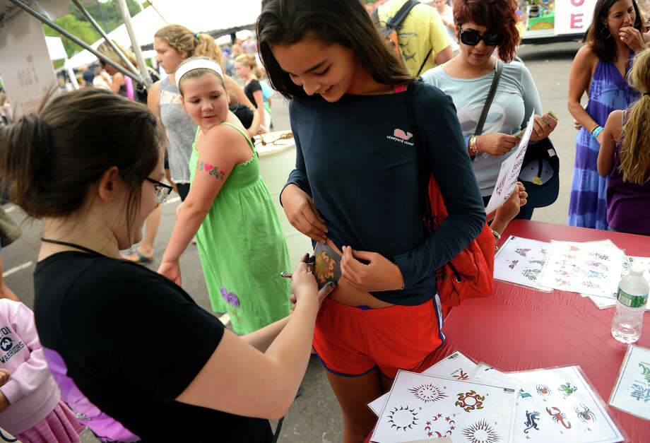 Audrey Adl, of New Canaan, gets an airbrush tattoo, at the 7th Annual Blues Views and BBQ Festival in Westport, Conn. on Saturday, Aug. 30, 2014. Photo: Christian Abraham / Connecticut Post