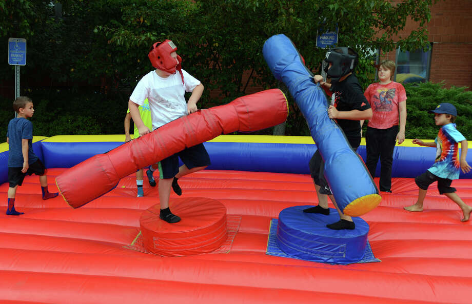 Cameron Yencik, 10, of monroe, at left, and his friend John Nawrocki, 11, of Stratford, play on one of the inflatables at the 7th Annual Blues Views and BBQ Festival in Westport, Conn. on Saturday, Aug. 30, 2014. Photo: Christian Abraham / Connecticut Post