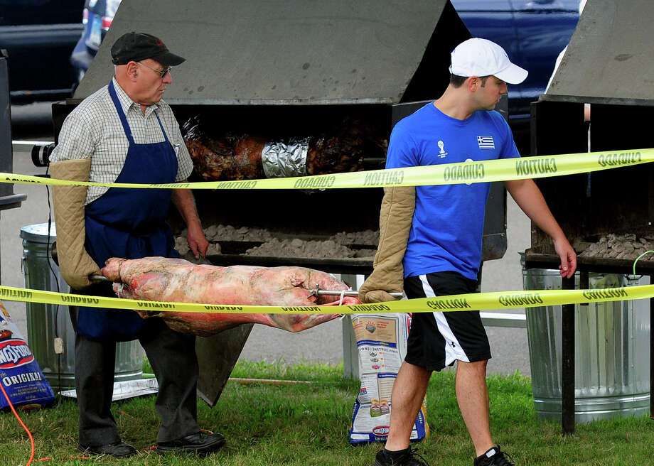 "Augustus Fifis, left, and Kosta Milas, prepare to BBQ a lamb during the annual ""Odyssey: A Greek Festival"" held at St. Barbara Greek Orthodox Church in Orange, Conn. on Saturday, Aug. 30, 2014. The festival continues on Sunday from noon to 10 p.m. and on Monday from noon to 8 p.m. Photo: Christian Abraham / Connecticut Post"