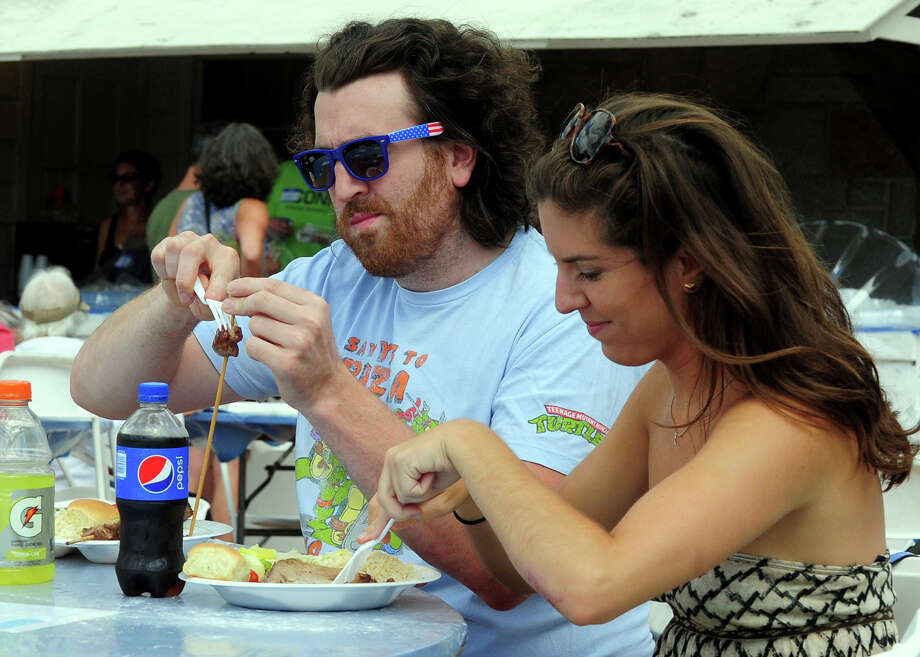 "Joe Padua and his girlfriend Kelsey Skura, both of New haven, have Greek food, during the annual ""Odyssey: A Greek Festival"" held at St. Barbara Greek Orthodox Church in Orange, Conn. on Saturday, Aug. 30, 2014. The festival continues on Sunday from noon to 10 p.m. and on Monday from noon to 8 p.m. Photo: Christian Abraham / Connecticut Post"