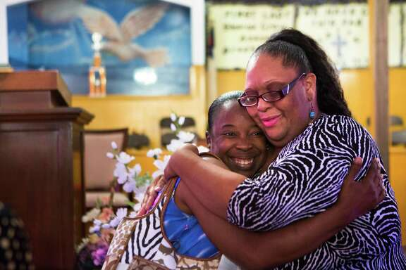 Tracy Chassion, right, receives a hug from her friend Shirley Harris-Swope at a prayer vigil in Houston Saturday. Chassion's 12-year-old daughter died two days after collapsing at an Alief school in 2010.