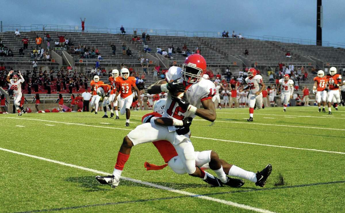 Alief Taylor tight end Anu Somoye (12) carries Bush defensive back Jordan Neale into the end zone for a 22-yard, game-winning touchdown during the second half of a high school football game, Saturday, August 30, 2014, at Mercer Stadium in Sugar Land, TX.