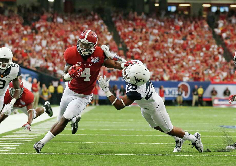 Alabama running back T.J. Yeldon fends off West Virginia cornerback Travis Bell (26) as he rushes for a touchdown in the first half of an NCAA college football game Saturday, Aug. 30, 2014, in Atlanta.  (AP Photo/ Brynn Anderson) Photo: Brynn Anderson, STF / AP