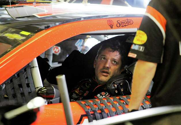 Sprint Cup Series driver Tony Stewart talks to a crew member during practice for Sunday