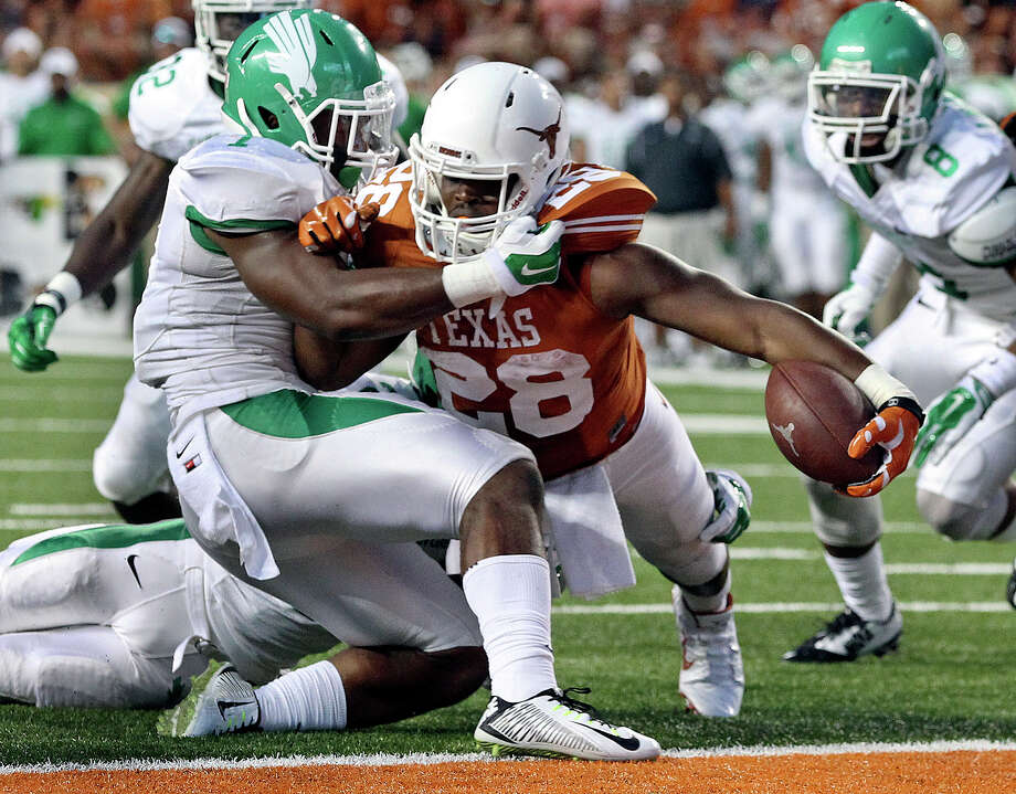 Texas' Malcolm Brown pushes the ball across the goal line for a second-quarter touchdown Photo: TOM REEL