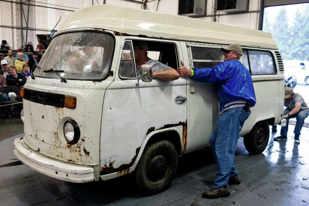 Struggling to control a Volkswagen bus with wet tires, an owner rolls in to auction off his vehicle.