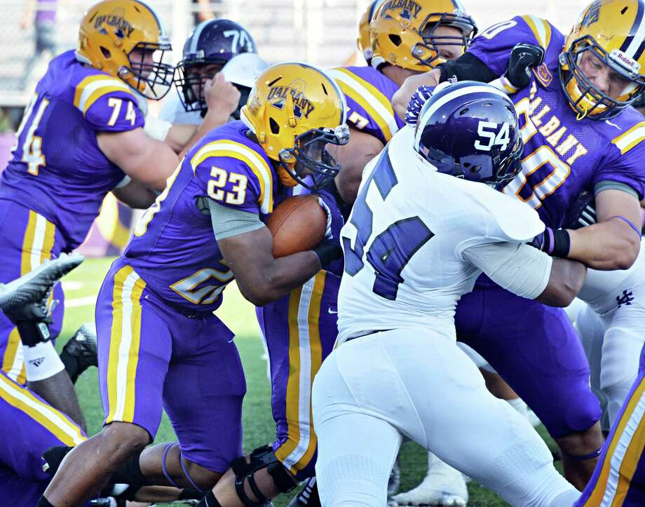 UAlbany's #23 Omar Osbourne center, looks for a hole opened by team mate #80 Brian Parker, right,  during Saturday's season opener against Holy Cross at Bob Ford Field in Albany, NY.   (John Carl D'Annibale / Times Union) Photo: John Carl D'Annibale / 00028391A
