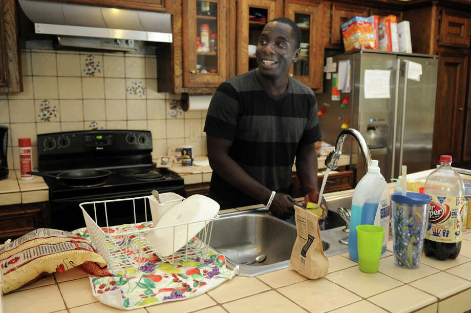 Resident John Gordon washes dishes in the kitchen at Angel Reach, a home in Conroe that houses youth that have aged out of foster care and have no home. Photo: Jerry Baker, Freelance