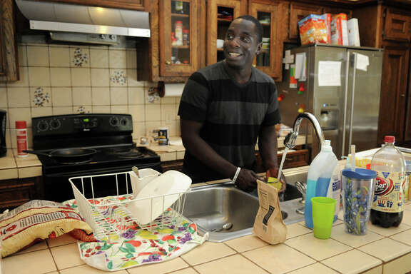 Resident John Gordon washes dishes in the kitchen at Angel Reach, a home in Conroe that houses young people who have aged out of foster care and have no home.
