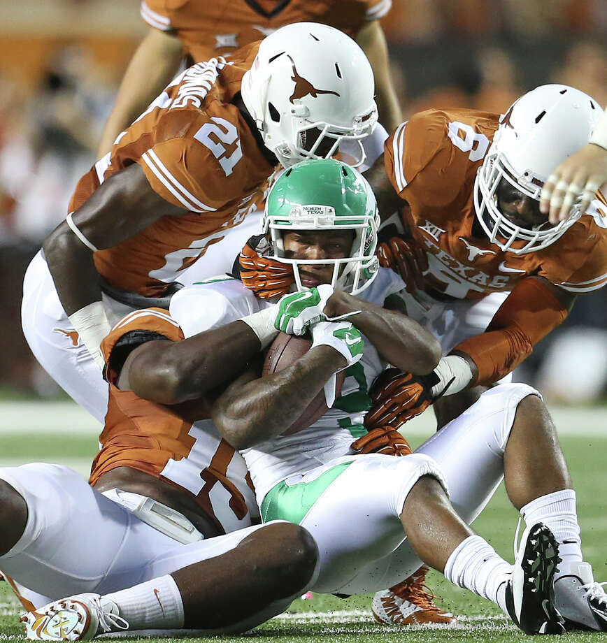 Longhorn defenders Duke Thomas (21), Bryson Echols (15) and Quandre Diggs smother Carlos Harris in the second quarter as UT hosts North Texas at Royal-Memorial Stadium on August 30, 2014. Photo: TOM REEL