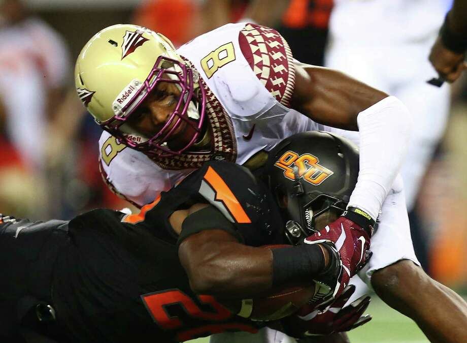 Oklahoma State's Desmond Roland is tackled by Florida State's Jalen Ramsey during the Seminoles' victory at AT&T Stadium. Photo: Ronald Martinez / Getty Images / 2014 Getty Images