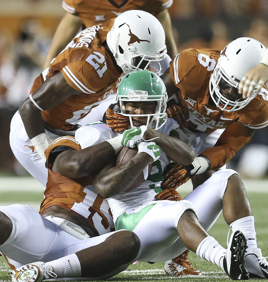 Texas' Duke Thomas (21), Bryson Echols (15) and Quandre Diggs smother North Texas' Carlos Harris during the second quarter of the Longhorns' victory at Royal-Memorial Stadium. Photo: Tom Reel / San Antonio Express-News