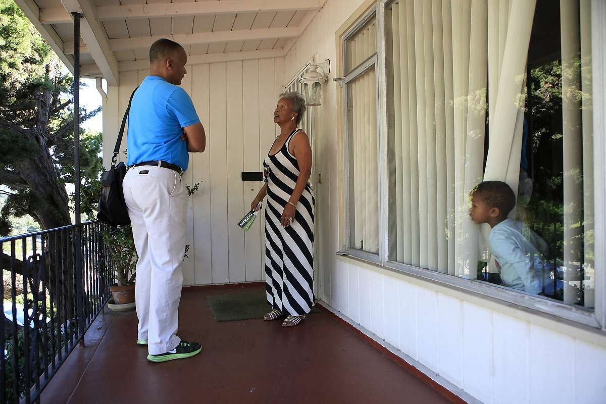A child peeks out of the window as mayoral candidate Bryan Parker talks with Shirley Littlejohn while canvassing in a neighborhood near Mills College in Oakland, CA, Saturday, August 23, 2014.