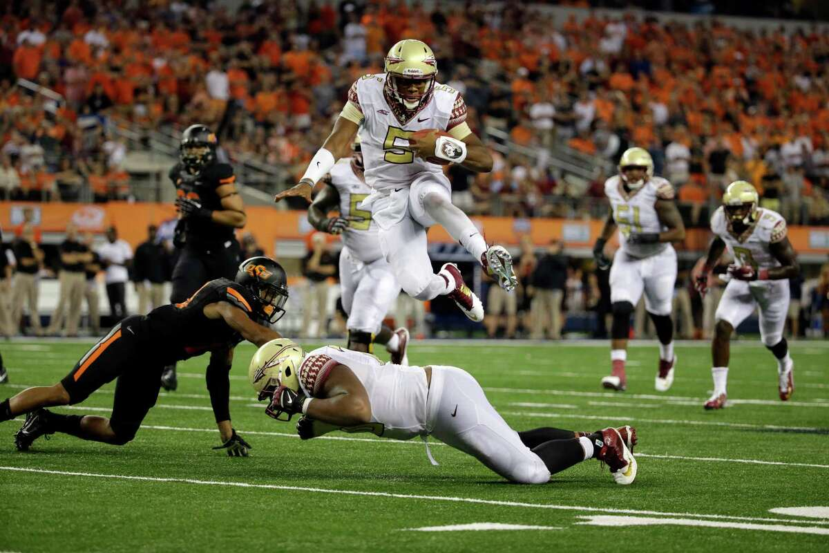 **RETRANSMISSION OF CBS118 FOR ALTERNATE CROP** Florida State quarterback Jameis Winston (5) leaps over guard Josue Matias, bottom, as Oklahoma State safety Jordan Sterns, left, is unable to stop Winston from reaching the end zone for a touchdown in the second half of an NCAA college football game, Saturday, Aug. 30, 2014, in Arlington, Texas. (AP Photo/Tony Gutierrez)