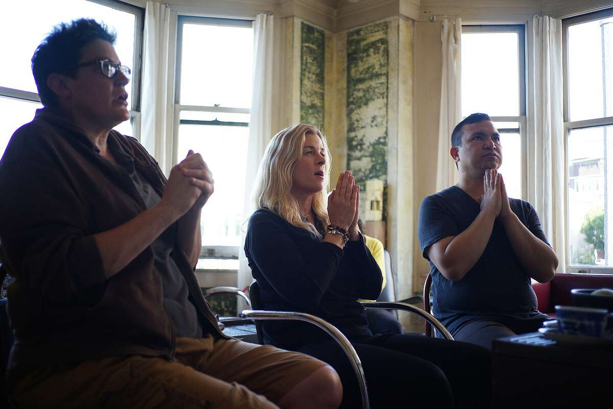 Left to right, Diana Elrod, Jacqui Naylor and Arthur Khu participate in Buddhist chants in Naylor's Gough St. apartment on Thursday, Aug. 21, 2014 in San Francisco, Calif. Naylor is currently facing an Ellis Act Eviction.